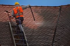 Roof washing. Man cleaning old tiles on the roof royalty free stock images