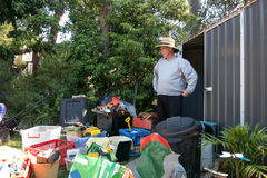 Man cleaning out shed. Man stunned by mess to be cleaned up out of garden shed Stock Images