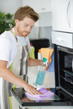 Man cleaning oven in kitchen. Man cleaning oven in the kitchen stock photo