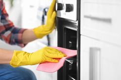 Man cleaning oven in kitchen,. Closeup stock photo