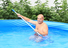 Man cleaning pool Stock Images