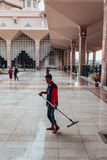 A man is cleaning in Putra Mosque in Wilayah Persekutuan Putrajaya, Malaysia.  Stock Photography