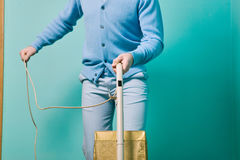 Man cleaning room with vintage vacuum cleaner. Against turquoise wall Royalty Free Stock Image