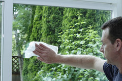 Man Cleaning a Sliding Glass Door. Adult male cleaning a clear glass sliding patio door with a paper towel and window washing fluid. There is a view outside into stock photography