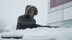 Man cleaning snow from car. With brush in living house district. Slow motion people footage stock video