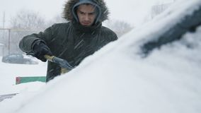 Man cleaning snow from car. With brush in living house district. Slow motion people footage stock footage