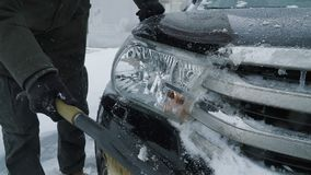 Man cleaning snow from car. Lights with brush. Slow motion people footage stock video footage