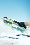 Man cleaning snow from car windshield with brush Royalty Free Stock Photo