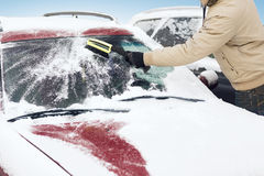 Man cleaning snow from car windshield with brush Royalty Free Stock Photography