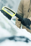 Man cleaning snow from car windshield with brush Royalty Free Stock Images