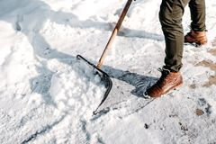 Man cleaning snow from house alley. Details of male using snow shovel. Adult cleaning snow from house alley. Details of male using snow shovel stock image