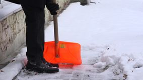 Man cleaning the snow with a shovel. 4K