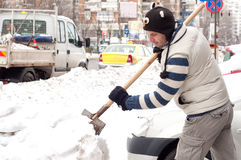 Man cleaning the snow with a shovel near his car Royalty Free Stock Photos