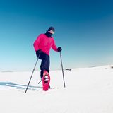 Man cleaning snowshoe. Winter tourist with snowshoes walk in snow Stock Photography