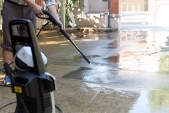 Man cleaning stone with high pressure water jet stock photo