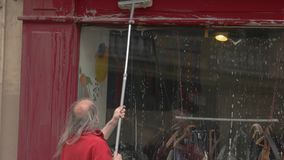 Man is cleaning storefront. stock video footage