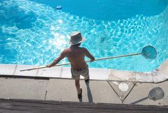 Man cleans swimming pool stock image