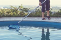Man cleaning swimming pool Royalty Free Stock Photo