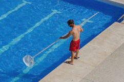 Man cleaning the swimming pool Stock Photography