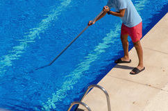 Man cleaning the swimming pool with a telescopic pole Royalty Free Stock Photo