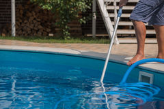 Man cleaning the swimming pool with vacuum cleaner. Man cleaning blue swimming pool with vacuum cleaner, closeup Royalty Free Stock Photo
