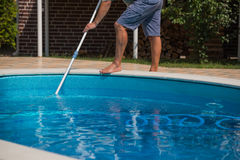 Man cleaning the swimming pool with vacuum cleaner, closeup. Man cleaning the swimming pool with equipment Royalty Free Stock Images
