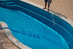 Man cleaning the swimming pool with vacuum cleaner. Suny day Royalty Free Stock Images