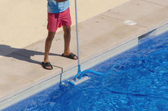 Man cleaning the swimming pool with a vacuum head Stock Photos