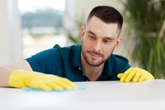 Man cleaning table with cloth at home Stock Photography