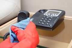 Man cleaning telephone with blue cloth Royalty Free Stock Image