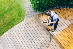 Man cleaning terrace with a power washer - high water pressure c. Leaner on wooden terrace surface stock photography