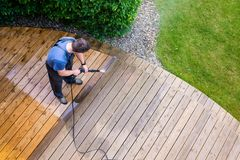 Man cleaning terrace with a power washer - high water pressure c. Leaner on wooden terrace surface royalty free stock photo