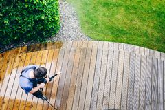 Man cleaning terrace with a power washer - high water pressure c stock image