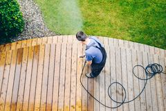 Man cleaning terrace with a power washer - high water pressure c. Leaner on wooden terrace surface royalty free stock photos