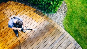 Man cleaning terrace with a power washer - high water pressure c. Leaner on wooden terrace surface royalty free stock images