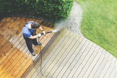 Cleaning terrace with a power washer - high water pressure clean. Man cleaning terrace with a power washer - high water pressure cleaner on wooden terrace royalty free stock image