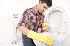 Man cleaning toilet with spray cleaner. Stock Photography