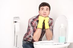 Man cleaning toilet with spray cleaner. Royalty Free Stock Images
