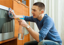 Man cleaning TV Royalty Free Stock Photography