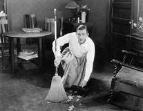 Man cleaning up with a broom. (All persons depicted are no longer living and no estate exists. Supplier grants that there will be no model release issues Royalty Free Stock Photo