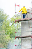 Man cleaning wall. Scaffolding Stock Photo