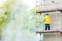 Man cleaning wall. Scaffolding Royalty Free Stock Image