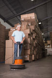 Man cleaning warehouse floor with machine Royalty Free Stock Image