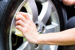 Man cleaning wheel rim while car wash Royalty Free Stock Photo