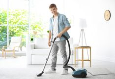 Man cleaning white carpet with vacuum in living room Stock Images