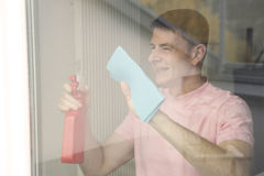 Man cleaning a window Stock Images