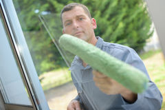 Man cleaning window pane. Man cleaning a window pane Royalty Free Stock Photo