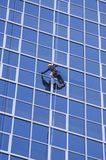 Man cleaning windows of modern business building