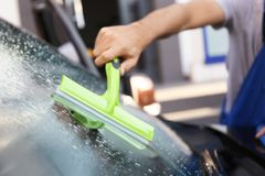 Man cleaning windscreen of car with squeegee. Outdoors Royalty Free Stock Photography
