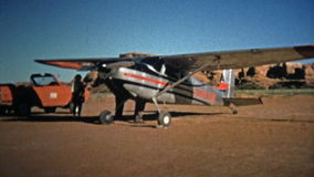 1971: Man cleaning the windshield of a small propeller touring airplane. stock video